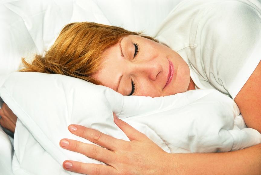 Happy woman sleeping on freshly cleaned duvet